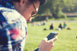 A man browsing through his smartphone in a park.